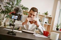 Tempo per il ritratto della prima colazione del blogger emozionante dell'alimento che mangia un panino mentre online scorrendo ne immagini stock libere da diritti