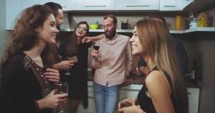 Tempo per una giovane società ciascuno del partito che chiacchiera tenendo un bicchiere di vino o alcune bevande, spendente un bu stock footage