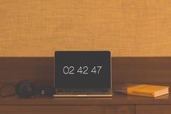 Tempo su un computer portatile con le cuffie e un libro fotografie stock libere da diritti
