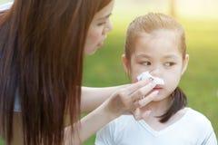 Temporada de gripe, nariz que sopla de la niña imagen de archivo