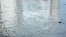 Temporal de lluvia pesado en la ciudad con las gotas de agua que caen en la tierra pavimentada y que salpican en charcos almacen de metraje de vídeo