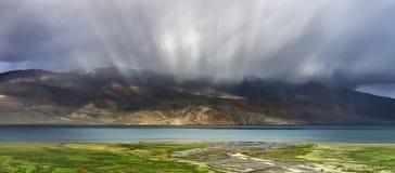 Temporale sul TSO Moriri del lago dell'alta montagna: i raggi del sole creano un bello effetto nelle nuvole sopra il lago, w blu Fotografia Stock