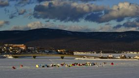Temporary ice fishing village set up at the mouth of a river in a picturesque eastern Canadian town. Temporary ice fishing village made up of rustic shacks set Stock Images