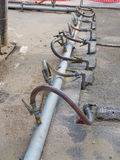 Temporary metal and plastic pipes with fittings  cross the road Royalty Free Stock Photos