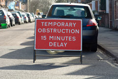 Temporary Obstruction 15 Minutes Delay sign on residential road Royalty Free Stock Images