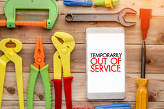Temporary out of service. Temporarily out of service concept with smart phone and handy tools pn wooden background royalty free stock image