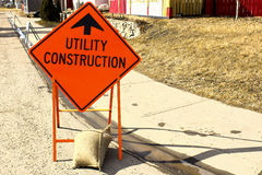 Temporary utility construction ahead sign beside a sidewalk.  stock photography