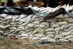 Temporary wall made of white sandbags and thick black nylon used as flood protection to prevent flooding of local family houses. Surrounded with rising flood stock images