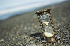Temporizzatore della sabbia su Pebble Beach Immagini Stock Libere da Diritti
