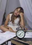 Temprano despertando Despertador que se coloca en la mesita de noche Despierte de una chica joven dormida en cama en un fondo Foto de archivo