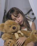 Temprano despertando Despertador que se coloca en la mesita de noche Despierte de una chica joven dormida que sostiene el oso de  Foto de archivo libre de regalías
