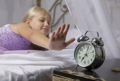 Temprano despertando Despierte de una chica joven dormida que para el despertador en una cama por la mañana Imagenes de archivo