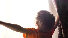 Temprano por la mañana el niño abre las cortinas, los rayos del sol pasa a través de la ventana Salida del sol metrajes