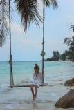 Temprano por la mañana la muchacha en el vestido blanco que balancea en el oscilación en la playa profundamente en pensamiento Fotos de archivo libres de regalías