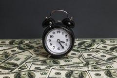 Temps - argent Concept d'affaires Heures analogues sur un tas de papier image stock