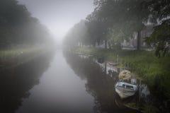 Temps brumeux dans le canal de ville de Breda avec le calme menteur de bateaux dans l'eau Image libre de droits