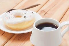 Temps chaud de boisson ou de coupure de matin de beignet doux et de café noir Photographie stock libre de droits