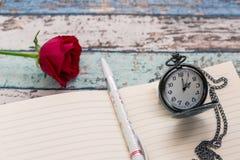Temps d'écriture pour l'amour : rose de rouge, journal, stylo, et montre de poche Photo libre de droits