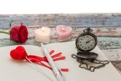 Temps d'écriture pour l'amour : rose de rouge, journal, stylo, et montre de poche Images libres de droits