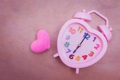 Temps d'amour : horloge de forme de coeur avec la vue supérieure de coeur rose Photo libre de droits