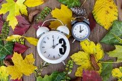 temps d'automne arrière de modification Deux horloges sur le fond de feuilles d'automne Images libres de droits