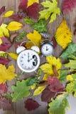 temps d'automne arrière de modification Deux horloges sur le fond de feuilles d'automne Photographie stock libre de droits