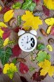 temps d'automne arrière de modification Deux horloges sur le fond de feuilles d'automne Photo libre de droits