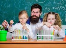 Temps d'?cole Écolières jugeant des tubes à essai guidés par le professeur Écoliers exécutant l'expérience dans la science image stock