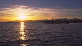 Temps de coucher du soleil et phare gauche dans le village de pêche méditerranéen de Cambrils, Espagne banque de vidéos