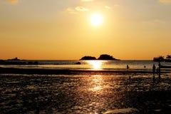 Temps de coucher du soleil sur l'île avec le fond orange de ciel Photographie stock libre de droits
