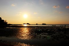 Temps de coucher du soleil sur la plage avec le fond orange de ciel Photographie stock libre de droits