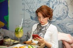 Temps de déjeuner Belle femme d'affaires adulte regardant le téléphone portable dans le restaurant images stock