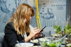 Temps de déjeuner Belle femme d'affaires adulte regardant le téléphone portable dans le restaurant image stock