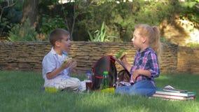 Temps de déjeuner, les enfants affamés sortent rapidement des sandwichs des conteneurs de nourriture et de consommation sur la pe clips vidéos