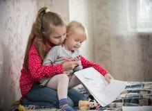 Temps de dépense de deux filles à la maison dessinant avec des marqueurs photos stock