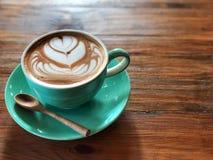 Temps de détente Café d'art de Latte dans la tasse verte et la cuillère en bois Image stock