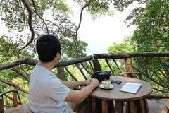 Temps de liberté du jeune homme asiatique heureux reposant et regardant la belle nature Images stock