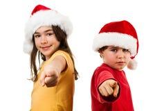 Temps de Noël - fille et garçon avec le pointage de Santa Claus Hat Image stock
