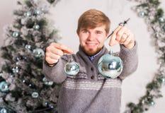Temps de Noël - jeune homme tenant des boules de Noël Images stock