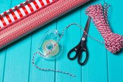 Temps de partie d'emballage cadeau de Noël avec le papier coloré, arcs de ruban, ciseaux a Photo libre de droits
