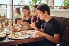 Temps de pizza Jeunes amis appréciant la pizza et la salade dans un café extérieur photographie stock libre de droits