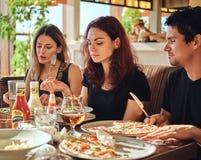 Temps de pizza Jeunes amis appréciant la pizza et la salade dans un café extérieur photo stock