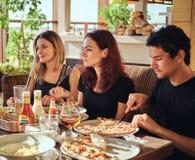 Temps de pizza Jeunes amis appréciant la pizza et la salade dans un café extérieur images stock