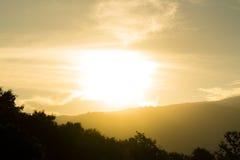 Temps de soirée de silhouette éclairé à contre-jour par montagne et de lumière du soleil Photos libres de droits