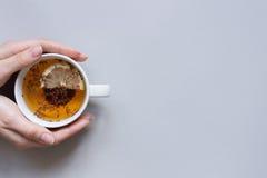 Temps de thé Mains tenant la tasse de thé noir chaud sur le fond bleu, vue supérieure Images stock