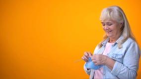 Temps de tricotage femelle d'écharpe, de passe-temps et libre de retraité heureux, aide gouvernementale photo libre de droits