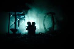temps et concept d'amour Les silhouettes des chiffres en céramique de jouet étreignant entre les sabliers dans l'obscurité ont al Images libres de droits