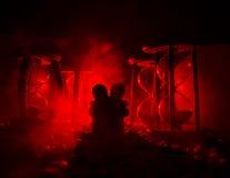 temps et concept d'amour Les silhouettes des chiffres en céramique de jouet étreignant entre les sabliers dans l'obscurité ont al Images stock