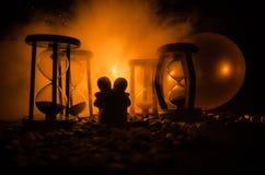 temps et concept d'amour Les silhouettes des chiffres en céramique de jouet étreignant entre les sabliers dans l'obscurité ont al Photos stock
