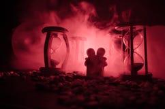 temps et concept d'amour Les silhouettes des chiffres en céramique de jouet étreignant entre les sabliers dans l'obscurité ont al Photographie stock